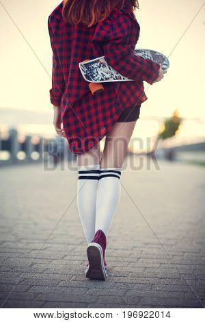 Girl skateboarder legs skateboarding at sunset