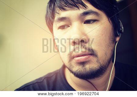 Asian man having a mustache beard and wear a headphone.