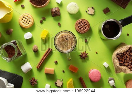 cup of coffee and ingredients at green paper background