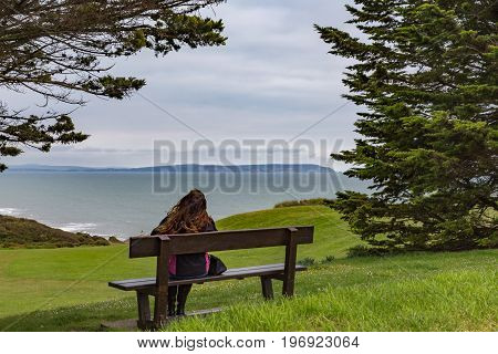 Young lady sitting on a bench looking out to sea on a cloudy day.