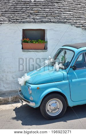 Old light blue tiny cute italian car decorated for marriage parcked outside an old trulli house from Alberobello south Italy