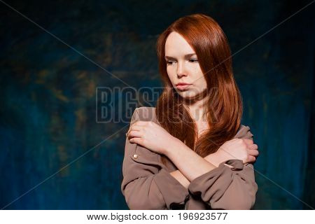 Dissatisfaction red-haired girl in brown shirt posing. beauty model woman with luxurious red hair. hairstyle. holiday makeup