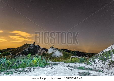 Starry night sky over the white chalky mountains. Natural landscape. Night view of the chalk hills. Archaeological monument - Krapivinskaya settlement Belgorod region Russia.