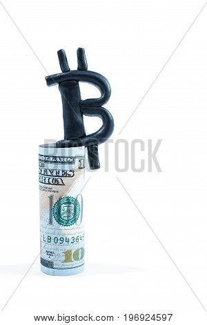 Bitcoin plasticine sign on top of the rolled-up dollar isolated on white background