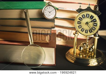 Literature concept. Magnifying glass near vintage clocks and old books against black background