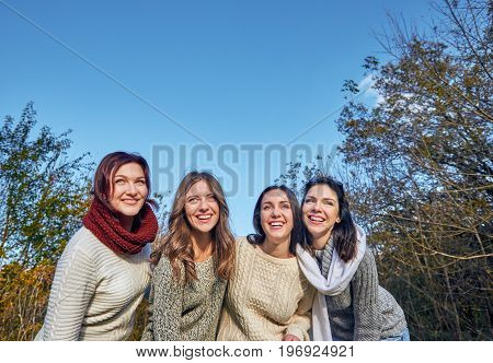 Group of cheerful young people posing and smiling in the park