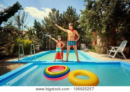 Father and son in suits of superheroes in the pool in the summer.