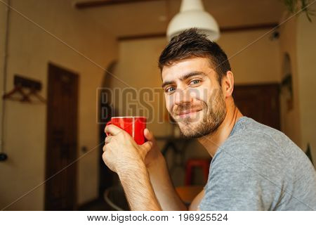 Man holding red cup of coffee in hand close up