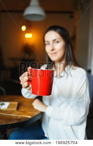 Red Cup Of Coffee In The Hands Of A Beautiful Smiling Girl