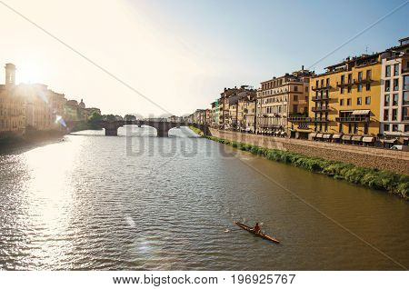 Florence, Italy - May 14, 2013. Overview of rower on the river Arno, bridge and buildings at sunset. In the city of Florence, the famous and amazing capital of the Italian Renaissance. Located in the Tuscany region. Retouched photo