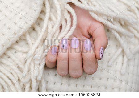 Beautiful female hand with light purple nail design. Dandelion nail art.
