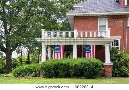 old brick home with hanging American flags on porch