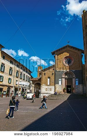 Orvieto, Italy - May 17, 2013. Overview of a square with old buildings, church and people under a blue sky in Orvieto, a pleasant and well preserved medieval town. Located in Umbria, central Italy