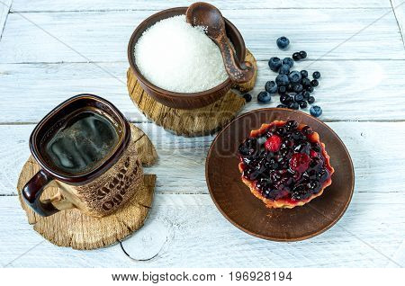 Cup Of Coffee And A Sweet Cake. Cake In A Basket Sprinkled With Berries.