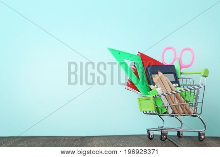 Shopping Cart With School Supplies On Wooden Table