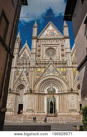 Orvieto, Italy - May 17, 2013. Facade view of the opulent and monumental Orvieto Cathedral (Duomo) with people in Orvieto, a pleasant and well preserved medieval town. Located in Umbria, central Italy