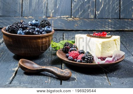A Bowl Of Berries And A Cheesecake. Multicolored Berries.