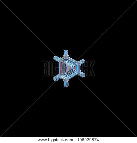 Snowflake isolated on black background. Macro photo of real snow crystal: tiny triangular snowflake with six simple straight arms and volume central triangle with simple pattern of lines and ridges.
