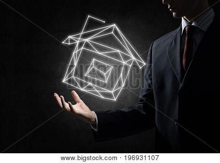 Close of buinessman holding in palm glowing house symbol