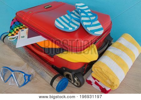 Suitcase with things for spending summer vacation. Anticipation of voyage. Women's clothes and accessories in red suitcase