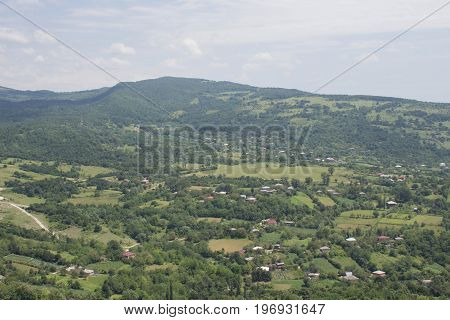 Beautiful small green village from above in Georgia. Village of houses in mountains