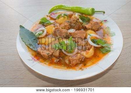 Tasty winter stew with meat and vegetables in bowl with ingredients over wooden table. Georgian cuisine