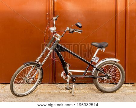 Custom tuned bicycle eco chopper style at a brown garage door background