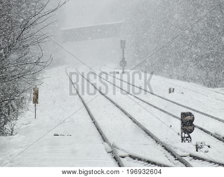 railway line in winter in heavy snow with signals and bridge