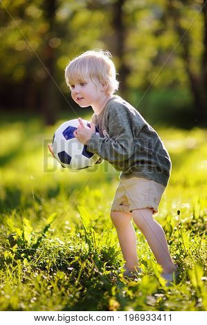 Little Boy Having Fun Playing A Soccer Game On Sunny Summer Day