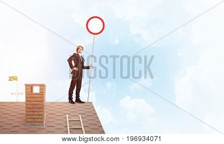 Businessman in suit and helmet holding round signboard. Mixed media