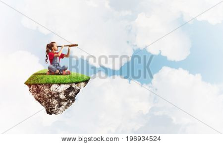 Cute smiling girl sitting on floating island high in sky