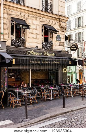 Paris France - June 22 2017: A traditional italian restaurant Florenza Pizzeria on the Montmartre Hill in Paris. Parisians and tourists enjoy food and drinks in the summer day.