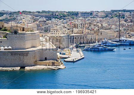 Fort Saint Angelo a large bastioned fort in Birgu Malta located at the centre of the Grand Harbour as seen from Upper Barracca Gardens with marina. It is best known for its role as the headquarters of Order of Saint John during the Great Siege of Malta.