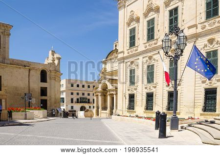 The Castille Place with Our Lady of Victories Chapel Roman Catholic Church of Saint Catherine of Italy and the Auberge de Castile et Leon with maltese and european flags in Valletta Malta.