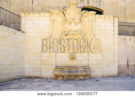 The baroque water well at the back wall of the House of the Annona at the Ordnance street in Valletta Malta