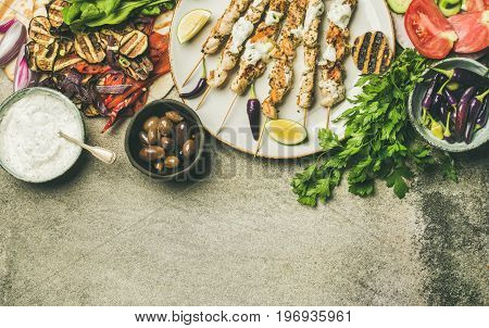 Summer barbecue party dinner set. Flatlay of grilled chicken skewers with yogurt sauce, flatbread, parsley, vegetables, marinated olives and chilis over grey concrete background, top view, copy space