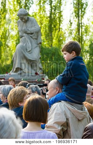 BERLIN - MAY 08 2015: Victory in Europe Day. Treptower Park. Anti-fascists in the commemoration ceremony near the sculpture of Motherland. A child sitting on the shoulders of his father.