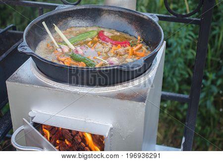 Uzbek pilaf is in a cast iron cauldron