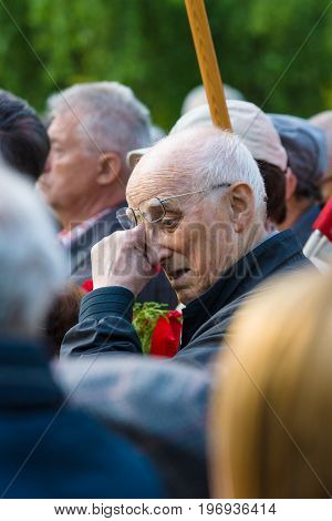 BERLIN - MAY 08 2015: Victory in Europe Day. Treptower Park. An elderly man a member of the commemorative ceremony wipes his away a tear.