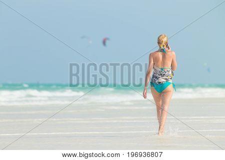 Happy woman having fun, enjoying summer, walking joyfully on tropical beach. Beautiful caucasian model wearing colorful scarf and turquoise bikini on vacations on Paje beach, Zanzibar, Tanzania