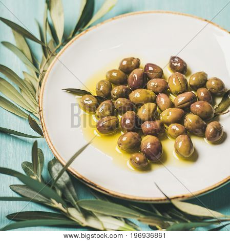 Pickled green Mediterranean olives in virgin oil on white ceramic plate and olive tree branch over light blue painted wooden background, selective focus, square crop