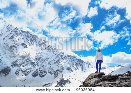 Mountain view.Blonde girl in the mountains. Sky with clouds