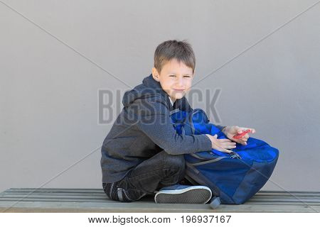 Boy with backpack and spinner sitting on the bench after school