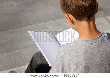 Boy reading book sitting on the stairs outdoors