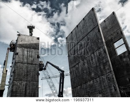 large highrise construction site with cranes and winches working on a concrete structure