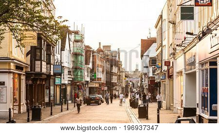 Canterbury Kent United Kingdom - June 16 2006: The High Street in Canterbury. Tourists visiting the historical city centre in the summer at sunset.