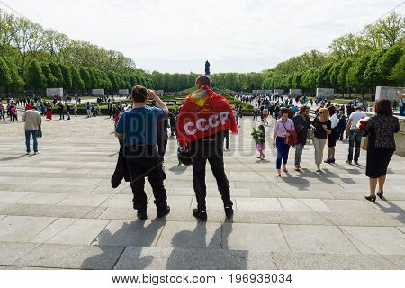 BERLIN - MAY 09, 2015: The man with the flag of the Soviet Union is on the background of Soviet War Memorial.