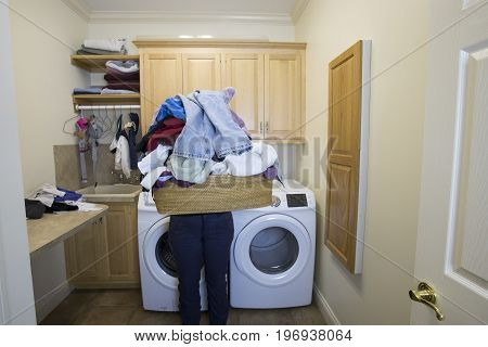 Woman Holding Basket Of Dirty Clothes In Laundry Room