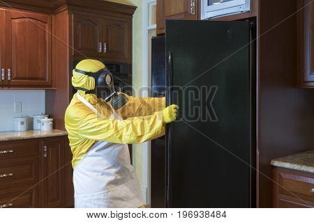 Mature Woman In Haz Mat Suit Looking In Refrigerator