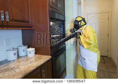 Mature Woman In Haz Mat Suit Opening Oven Door